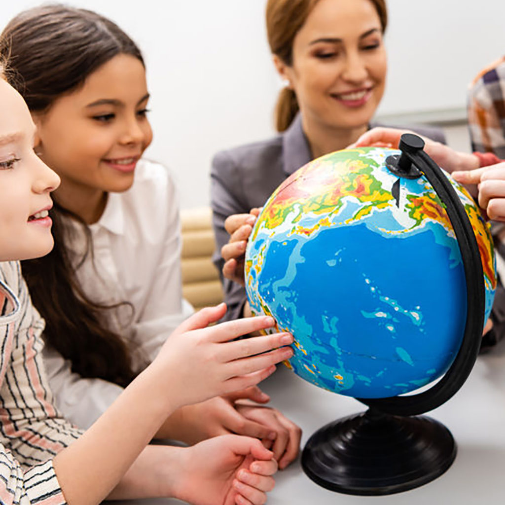 Cropped view of pupils and teacher looking at globe while studying geography in classroom