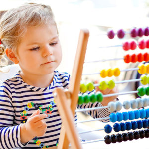 Adorable cute beautiful little toddler girl playing with educational wooden rainbow toy pyramid and counter abacus. Healthy happy baby learning to count and colors, indoors on sunny day